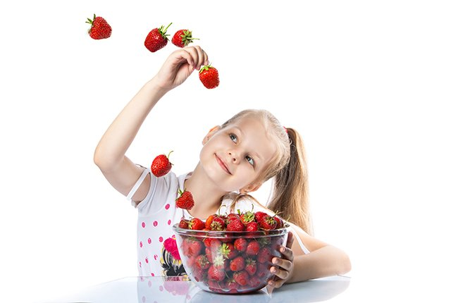 child with bowl of strawberries