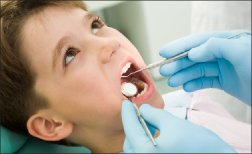 child with mouth open at dentist