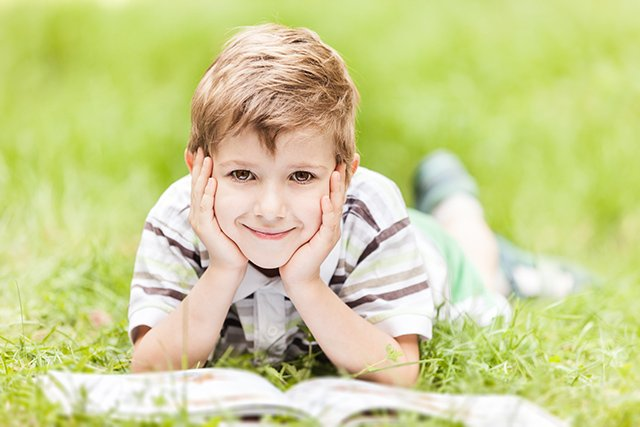 boy reading in grass