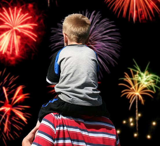 boy watching fireworks with father