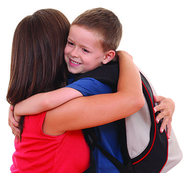 Mom hugging son with backpack