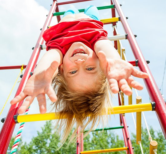 child upside down on playground
