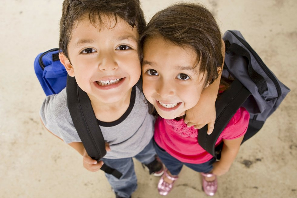 two kids hugging with backpacks