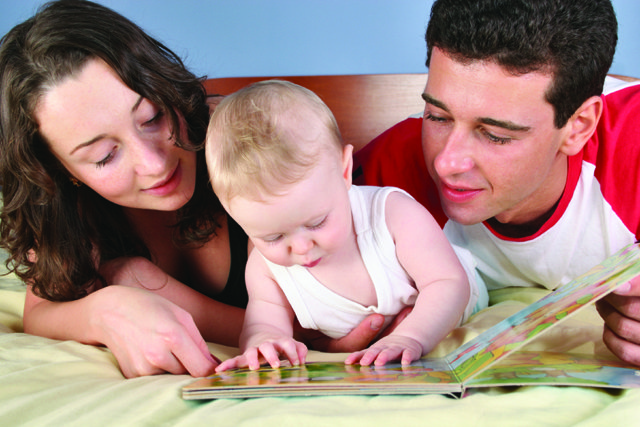 mom and dad reading to baby