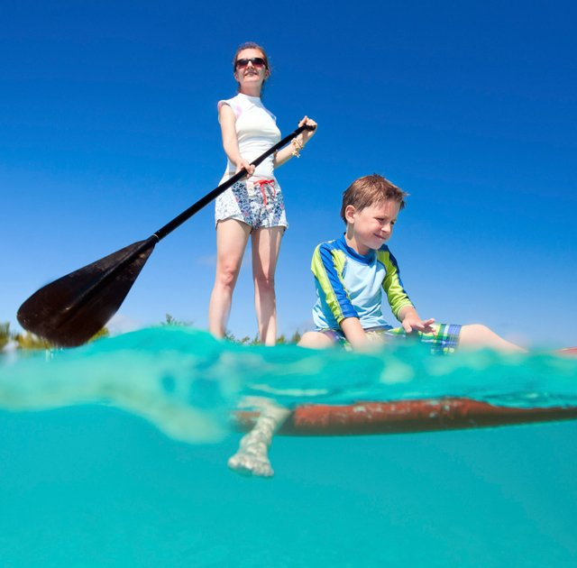 paddle boarding mother and son