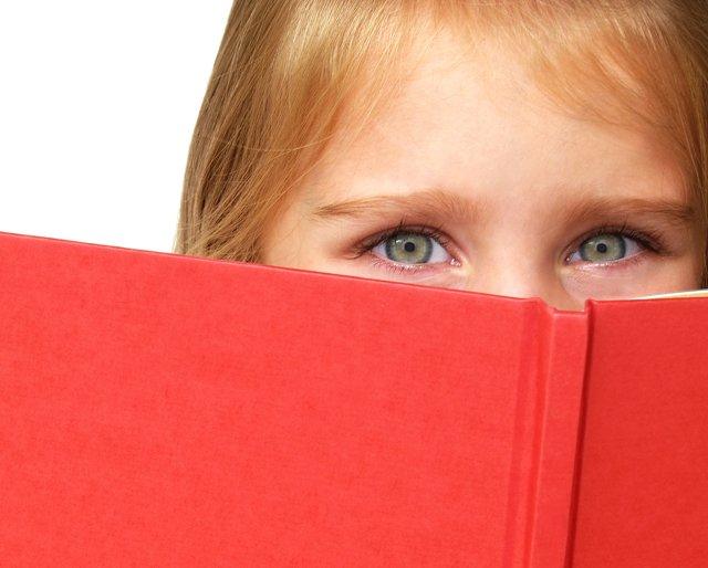 child hiding behind book
