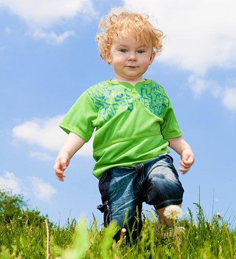 toddler boy walking in green field