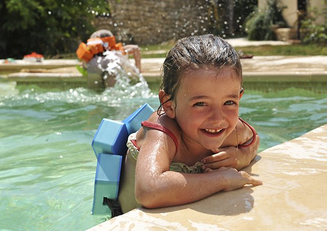 child in pool with safety gear