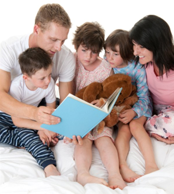 family reading book in bed