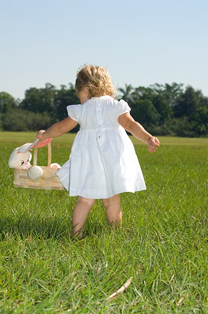 toddler girl in white in field with easter basket.jpg