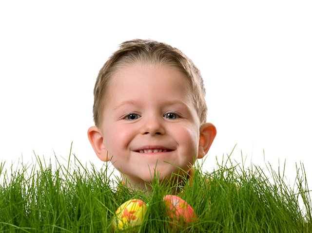 Little boy peeking over grass with easter egg