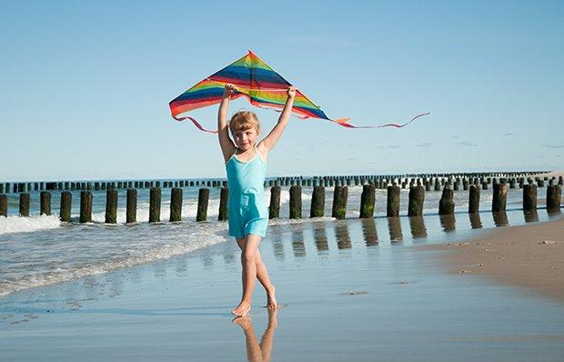 Child flying kite on beach