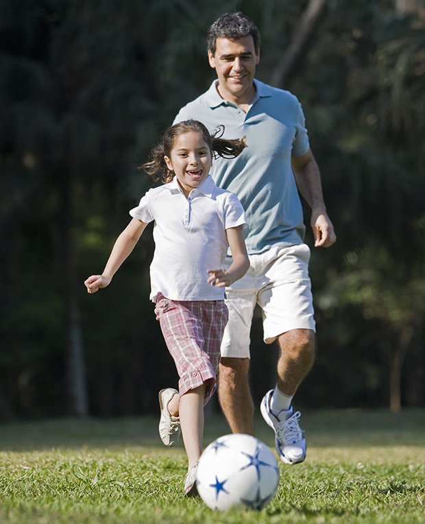 girl playing soccer with father