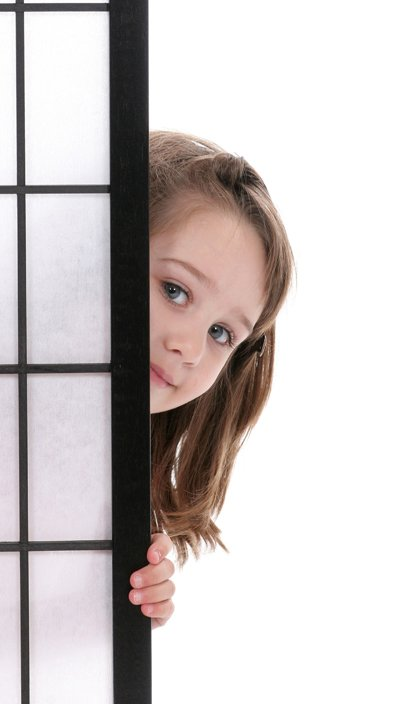 child peeking behind door